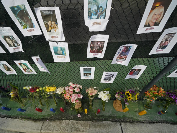 A memorial near the Champlain Towers South disaster site holds photos of missing persons in Surfside, Fla.