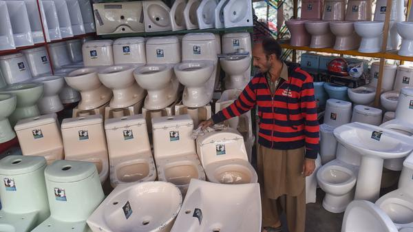 A Pakistani shopkeeper cleans toilets on display inside his shop in Lahore.