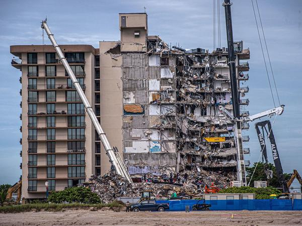 Search and rescue teams look for survivors Wednesday in the partially collapsed 12-story Champlain Towers South condo building in Surfside, Fla. Four more bodies were found on Wednesday.
