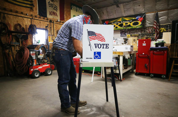 A voter marks his ballot at a polling place on Nov. 3 in Richland, Iowa. A new poll finds ensuring access to voting is more important than tamping down on voter fraud for most Americans.