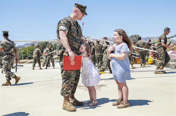 Joseph Hardebeck, a senior Navy corpsman, is greeted by his daughters Zoey, 9, and Adalie, 7, after receiving the Purple Heart at an award ceremony at Southern California's Camp Pendleton on Thursday.