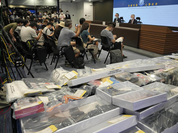 Police officials hold a news conference with confiscated evidence at police headquarters in Hong Kong on Tuesday. Police say they arrested nine people on suspicion of engaging in terrorist activity, after uncovering an attempt to make explosives and plant bombs across the city.