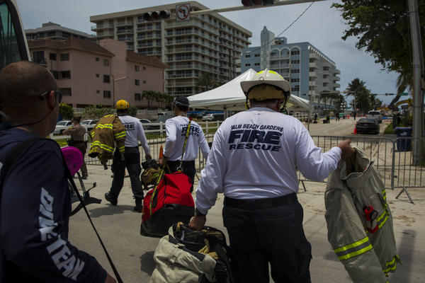 Fire rescue workers head toward the partially collapsed 12-story Champlain Towers South on Monday in Surfside, Fla.