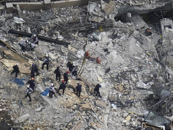 Rescue workers search in the rubble at the Champlain Towers South condo in Surfside, Fla., on June 26.