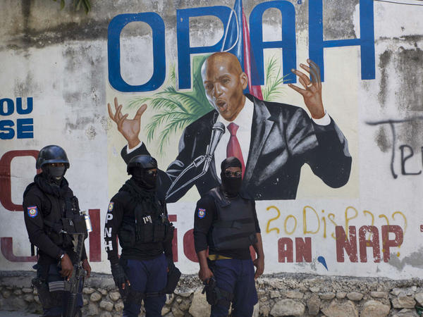 Police stand near a mural featuring Haitian President Jovenel Moïse near the leader's residence, where he was killed by gunmen in the early morning hours in Port-au-Prince, Haiti, on Wednesday.