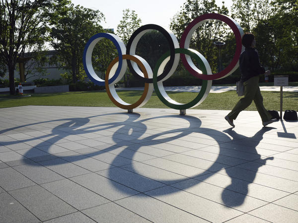 A woman passes the Olympic Rings near the National Stadium last month in Tokyo. There won't be any spectators at Olympic events in Japan's capital.