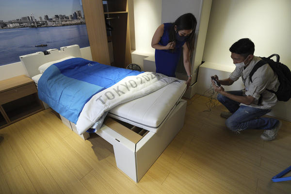 Journalists look at cardboard beds for the Tokyo 2020 Olympic and Paralympic at the Village Plaza near Tokyo 2020 Olympic and Paralympic Village Sunday, June 20, in Tokyo.