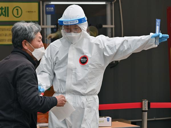A medical staffer wearing protective gear gestures after collecting a swab from a visitor to test for the coronavirus at a temporary testing station in Seoul in December 2020.  South Korea on Friday announced it would raise restrictions in the capital region to the highest level as a fourth wave of infections is gaining speed.