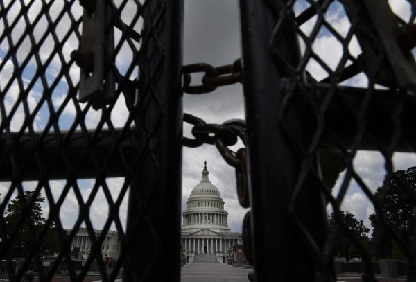 The U.S. Capitol is seen behind fences on July 9, the day crews began to take the temporary structure down.