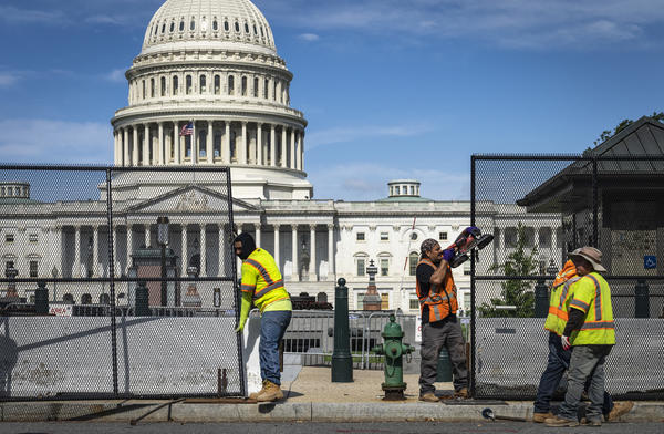 Workers remove security fencing surrounding the U.S. Capitol on Saturday.