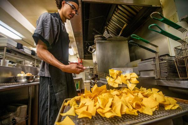 Brandon Ford removes tortilla chips from a frialator for the lunchtime crowd in the very busy kitchen at the Waterhouse Restaurant in Peterborough, NH. (Jesse Costa/WBUR)