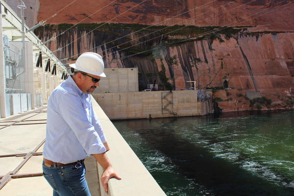 Bureau of Reclamation Glen Canyon Dam manager, Bob Martin, stands on a ledge overlooking the Colorado River as it leaves Lake Powell.