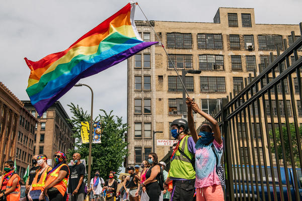 A woman waves a rainbow flag during a Pride march in June 2020 in Minneapolis, Minnesota.