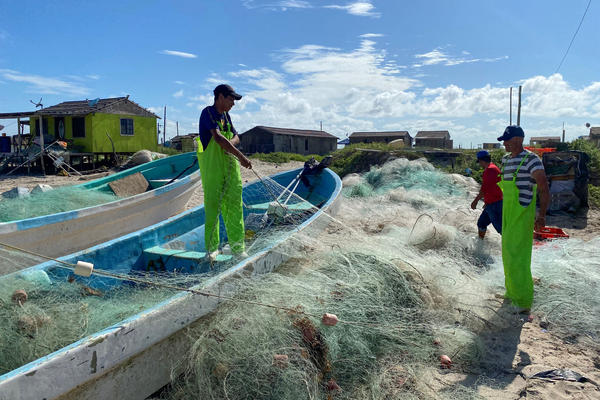 Mexican fishermen tend to their nets on Playa Bagdad (Bagdad Beach), just south of the Texas-Mexico border. Poaching of red snapper in the Gulf of Mexico is a multimillion-dollar black market.
