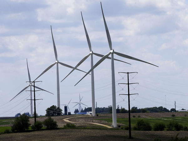 Wind turbines in a field in Adair, Iowa. Democrats' budget deal would use financial carrots and sticks to encourage utilities to shift to clean energy.