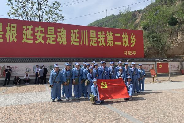 """Tourists dressed up as People's Liberation Army soldiers pose in Liangjiahe village, where a teenage Xi Jinping spent seven years doing hard labor. Today the village is a popular red tourism site. The sign displays a quote from Xi: """"Liangjiahe is where my roots are, and my soul. It is my second home."""""""