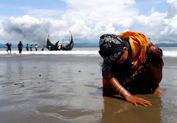An exhausted Rohingya refugee woman touches the shore after crossing the Bangladesh-Myanmar border by boat through the Bay of Bengal, in Shah Porir Dwip, Bangladesh, on Sept. 11, 2017.