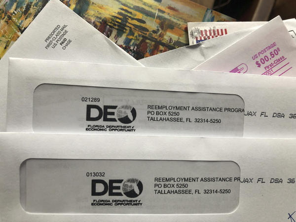 Envelopes from the Florida Department of Economic Opportunity Reemployment Assistance Program are shown, Thursday, Nov. 5, 2020, in Surfside, Fla. Through April 2021, Florida has regained about half the number of jobs lost in March and April of 2020.  (AP Photo/Wilfredo Lee)