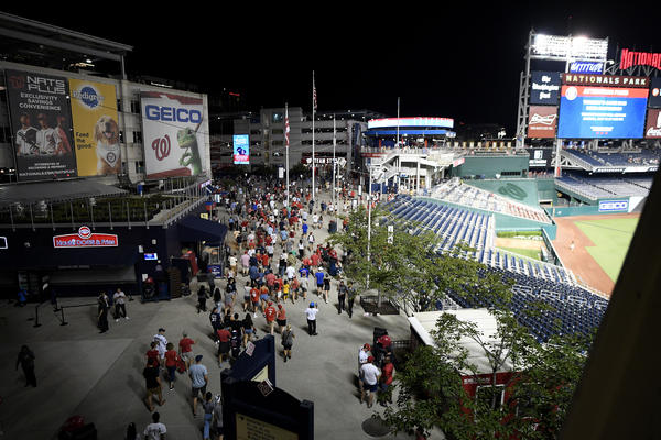 Spectators leave the stadium in the sixth inning of a baseball game between the Washington Nationals and the San Diego Padres on Saturday night in D.C. after a shooting occured outside the park.