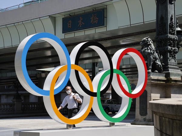 A man wearing a face mask walks past the Olympic Rings ahead of the Tokyo 2020 Olympic Games. The Games are scheduled to begin this week in Japan despite a global rise in coronavirus cases.