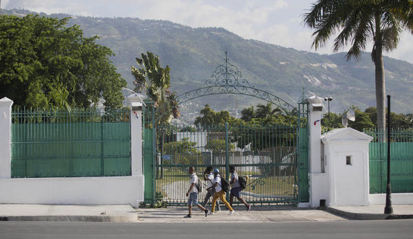 Pedestrians walk past the National Palace in Port-au-Prince, Haiti, Wednesday, July 7, 2021. A squad of gunmen assassinated Haitian President Jovenel Moise and wounded his wife in an overnight raid on their home Wednesday(AP Photo/Joseph Odelyn)