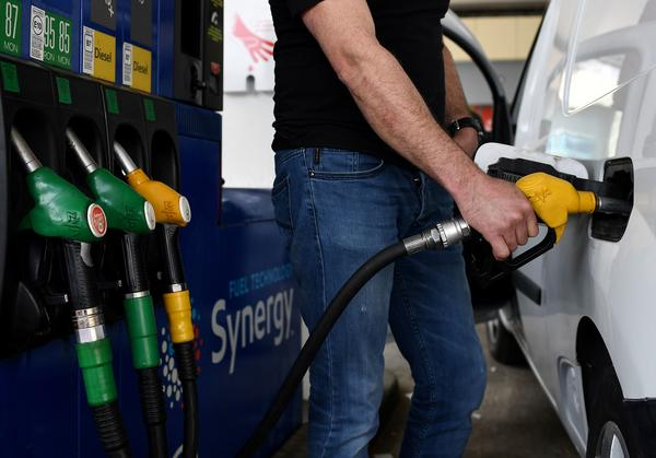 A man refuels his car in Paris in 2020. Men spend their money on greenhouse gas-emitting goods and services at a much higher rate than women, researchers found.