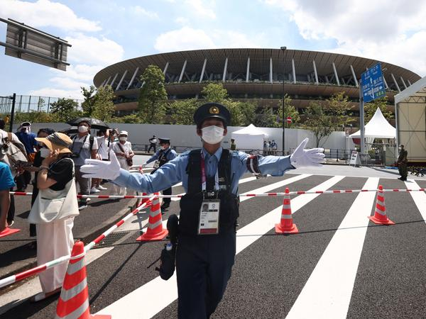 Police manage the crowd outside the Olympic Stadium in Tokyo on July 23, 2021, ahead of the opening ceremony of the 2020 Tokyo Olympic Games.