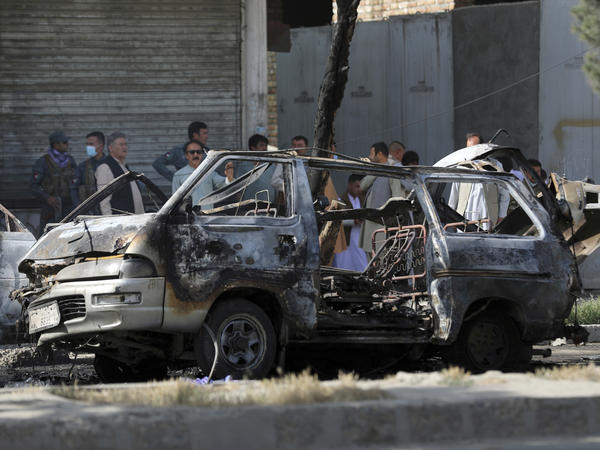 In this June 12, 2021 photo, Afghan security personnel inspect the site of a bomb explosion in Kabul, Afghanistan. In a report released Monday, the United Nations said that more women and children were killed and wounded in Afghanistan in the first half of 2021 than in any year since the UN began keeping count.