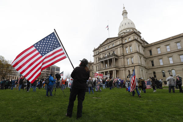 A protester holds an American flag on the lawn of the Michigan Capitol on April 30, 2020. Lawmakers in Shiawassee County are vowing to return $65,000 in bonuses they gave themselves using federal coronavirus relief funds.
