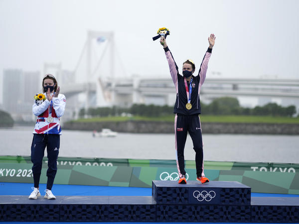 Gold medal winner Flora Duffy of Bermuda (center) celebrates her win in the triathlon on Tuesday, next to silver medalist Georgia Taylor-Brown of Great Britain.