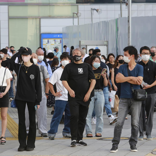People wearing face masks to protect against the spread of the coronavirus stand at an intersection in Tokyo on Tuesday.