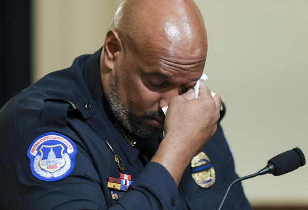 U.S. Capitol Police Pfc. Harry Dunn wipes his eye as he testifies during Tuesday's House select committee hearing on the Jan. 6 attack. During his testimony, Dunn said rioters hurled racial epithets at him and other Black officers.