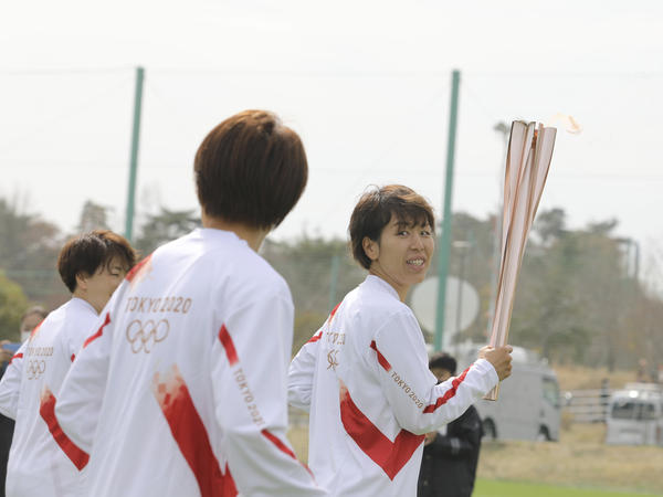 Azusa Iwashimizu (right) and other members of Japan women's national football team run as torchbearers in the first leg of the torch relay for Tokyo Olympics on Thursday in Fukushima prefecture, Japan.