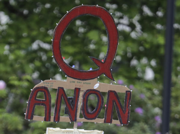 A person carries a sign supporting QAnon during a May 2020 protest rally in Olympia, Wash.