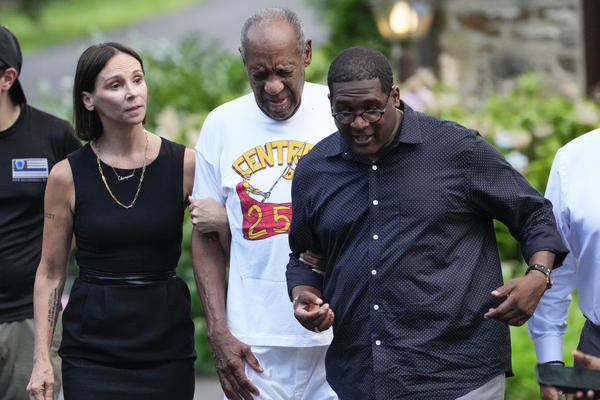 Bill Cosby (center) approaches members of the media gathered outside his home in Cheltenham, Pa., with his spokesperson Andrew Wyatt. On Wednesday, Pennsylvania's highest court overturned Cosby's sex assault conviction, and he was released from prison.