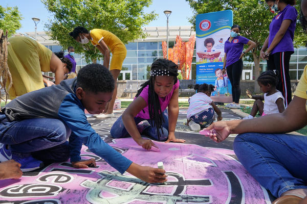Children and teachers from the KU Kids Deanwood child care center in Washington, D.C., complete a mural in celebration of the launch of the child tax credit.