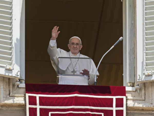 Pope Francis salutes the crowd as he arrives for the Angelus noon prayer from the window of his studio overlooking St. Peter's Square at the Vatican on Sunday.