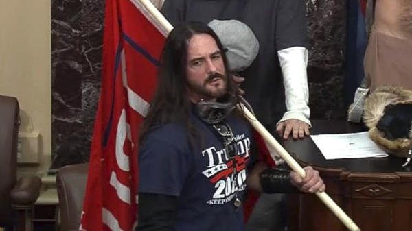 In this image from U.S. Capitol Police video, Paul Hodgkins of Tampa, Fla., stands in the well on the floor of the U.S. Senate on Jan. 6. On Monday, he was sentenced to eight months in prison.