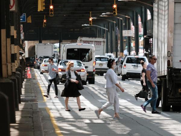 People walk along a main street in Brighton Beach, Brooklyn on Thursday in New York City.