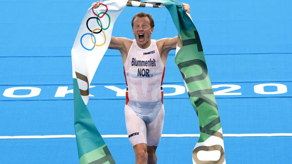 Norway's Kristian Blummenfelt celebrates as he crosses the line Monday to win the men's triathlon at the Tokyo Olympics. Blummenfelt won after a miscommunication between a media boat and the starting officials caused a rare false start in the endurance race.