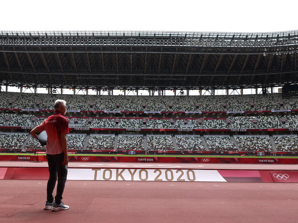 A passerby looks on while wearing a protective face covering inside an empty Olympic Stadium, host to the Athletics competition, at the Tokyo Olympic Games on Thursday.