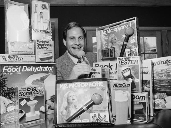 In this 1982 file photo, Ron Popeil, the man behind those late-night, rapid-fire television commercials that sell everything from the Mr. Microphone to the Pocket Fisherman to the classic Veg-a-Matic, sits surrounded by his wares in his office in Beverly Hills, Calif. Popeil died Wednesday, his family said.