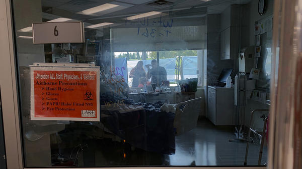 Family members gather outside the window of a COVID-19 patient at Lake Regional Hospital in Osage Beach, Mo., on Monday.