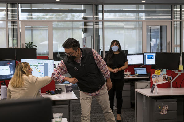 Employees elbow bump at a JLL office in Menlo Park, Calif., in September. With the delta variant surging, mask mandates are returning, and some employers are now requiring employees to be vaccinated before coming to the office.