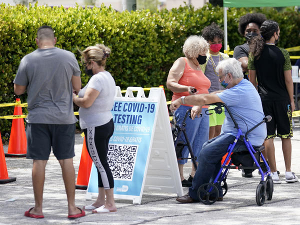 People wait in line at a Miami-Dade County COVID-19 testing site, Monday, July 26, 2021, in Hialeah, Fla. Florida accounted for a fifth of the nation's new infections last week, more than any other state, according to the CDC.
