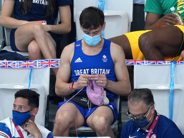 Great Britain's Tom Daley knits in the stands Sunday during the women's 3-meter springboard final at the Tokyo Aquatics Centre at the Olympic Games.