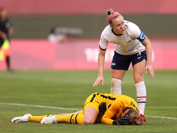 U.S. goalkeeper Alyssa Naeher lies injured as Becky Sauerbrunn checks on her during the women's semifinal match between Team USA and Canada on Monday at the Tokyo Olympic Games at Kashima Stadium.