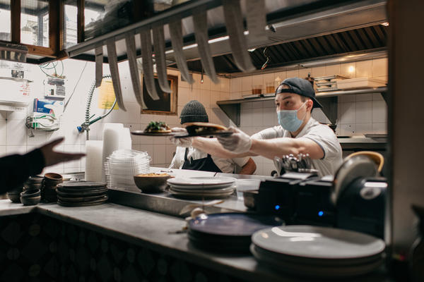 Masked kitchen workers pass plates of food to a server at Claro restaurant in February in New York City. Starting next month, those plates will go only to indoor diners who can prove they have been vaccinated.