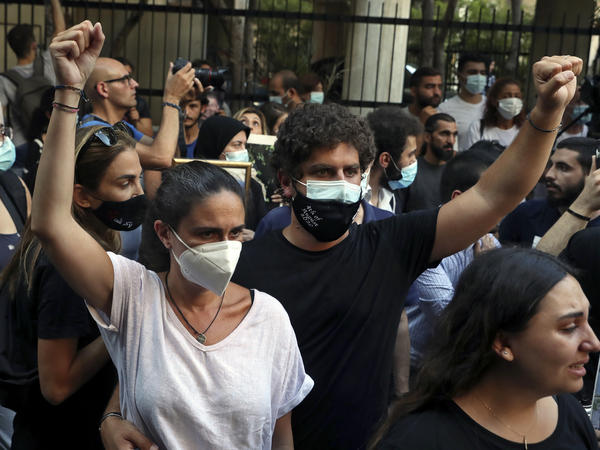 Tracy and Paul Naggear, the parents of 3-year-old Alexandra, who was killed in last year's massive blast, raise their fists during a protest outside the home of caretaker Interior Minister Mohamed Fehmi, in Beirut, July 13. A year after the deadly blast, families of the victims are seeking justice for their loved ones.