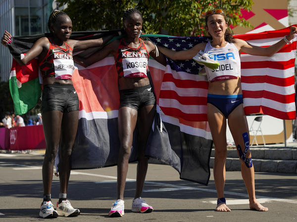 Gold medalist Peres Jepchirchir (left) of Kenya, stands with silver medalist and compatriot Brigid Kosgei, (center) and bronze medalist Molly Seidel (right) of the United States, after the women's marathon at the Summer Olympics in Sapporo, Japan.